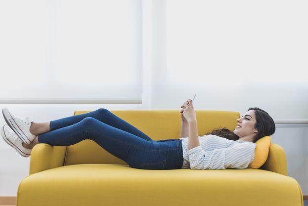 mulher deitada no sofá pode ter dor nas costas