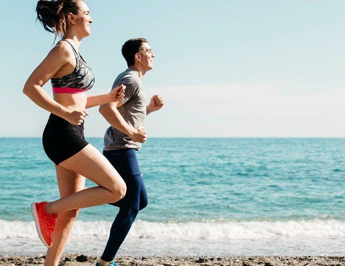 Pessoas correndo na areia da praia fazendo atividade físca