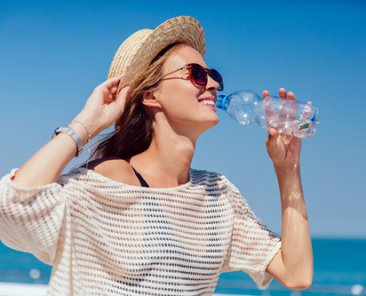 Summer photo of a happy pretty girl in sunglasses drinking clear water, during walking on quay, near the ocean. Dressed in stylish clothes and hat.