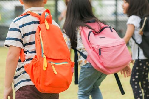 Crianças carregando peso nas mochilas